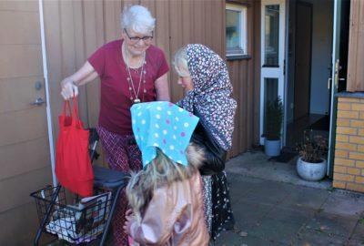 Äldre dam får godsaker av två påskkärringar