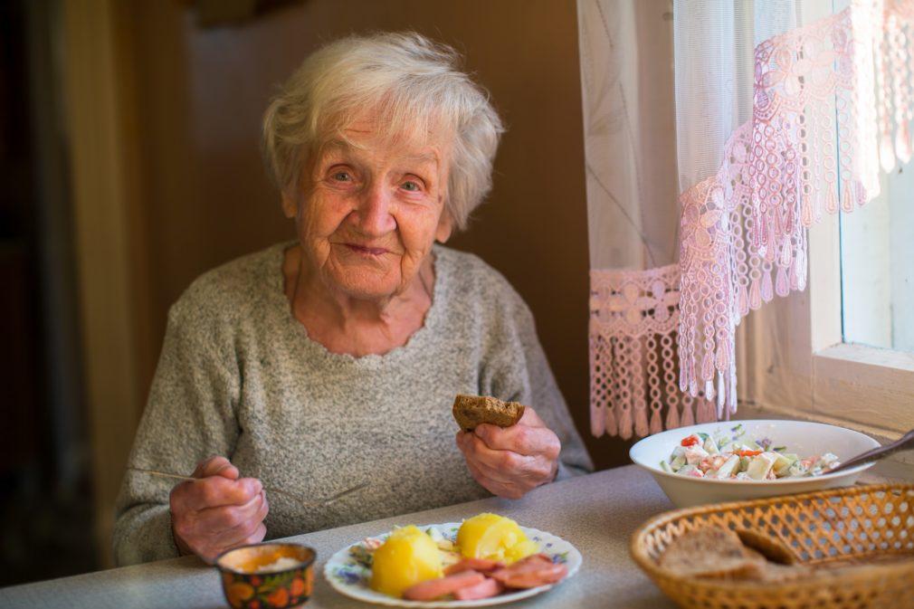 En äldre dam som ler, sittande vid ett dukat bord