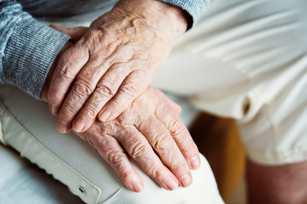 två äldre händer i kors, på ett ben.