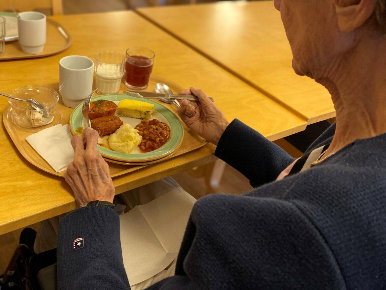 En äldre kvinna som sitter med en måltid framför sig.
